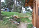 Vpravo chatka fungující jako zázemí pro kurzy, vlevo stanování pod borovicemi